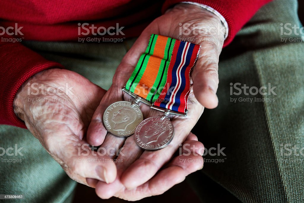 Old Soldier Holding His War Service Medals. stock photo