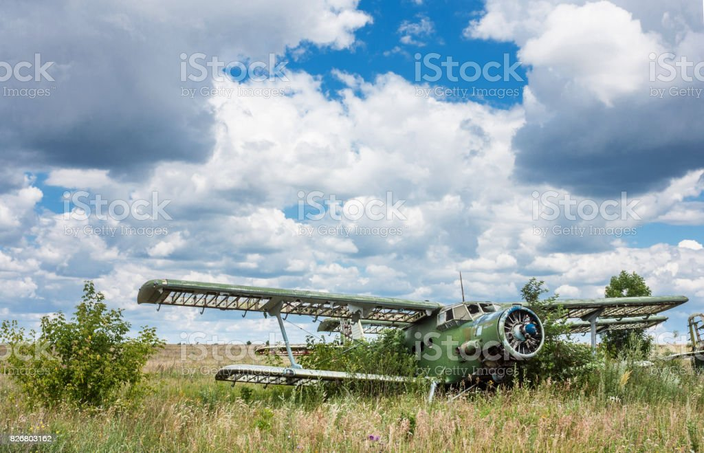 Old soviet biplane Antonov An-2 (Colt) aircraft on an abandoned airfield in Ukraine stock photo