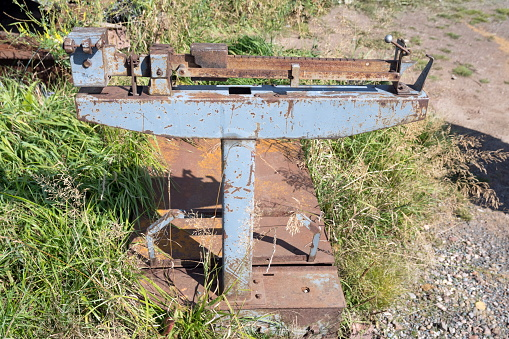 Old Soviet mechanical freight scales stand on the grass in summer.