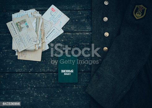 istock Old Soviet military ID card with the letters on the wooden table. 642336956