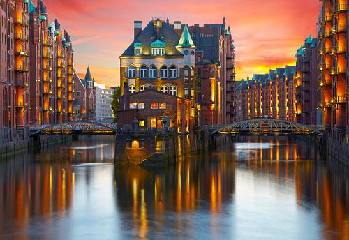 Old Speicherstadt in Hamburg illuminated at night. Sunset backgr