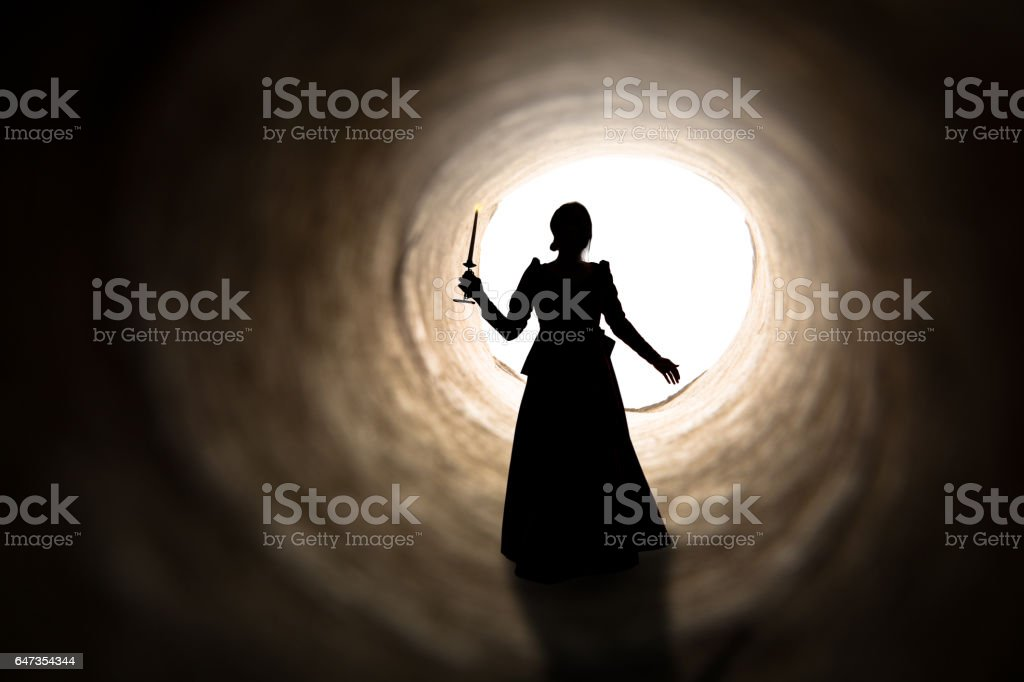 Old Spirit Drifting Toward Light In Tunnel A silhouette of a woman in vintage dress holding a candle as she walks toward the light at the end of a tunnel. 19th Century Style Stock Photo