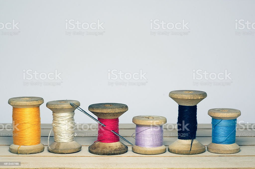 Old spool of thread with needle.  cloth making. stock photo