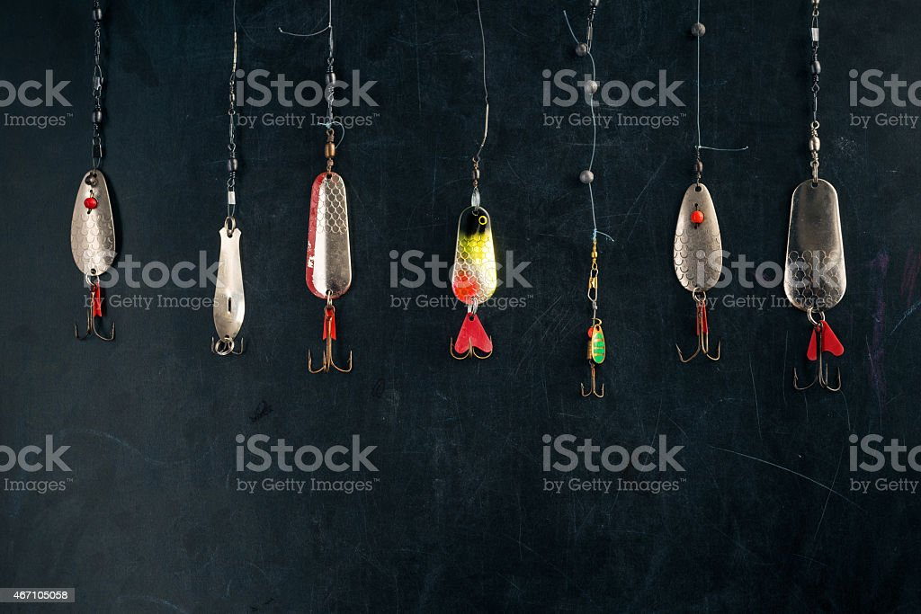 old spoon lures on black board stock photo