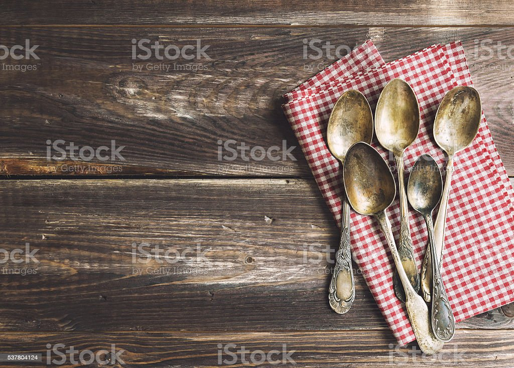Old spoons piled on rustic wooden background stock photo