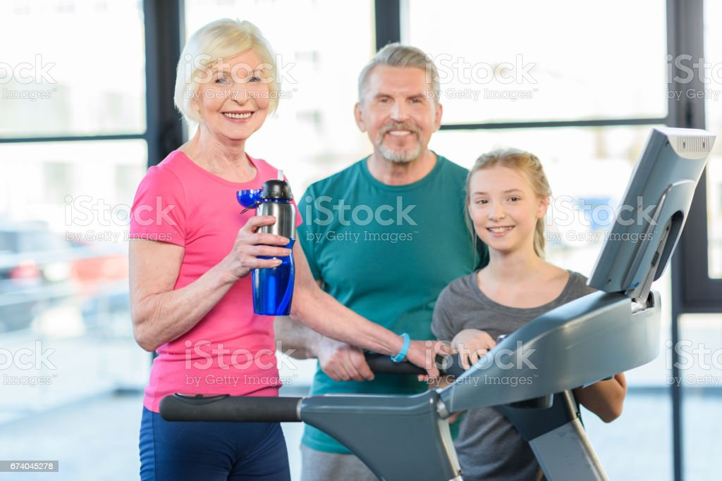 old sport couple and girl training on treadmill in fitness class royalty-free stock photo
