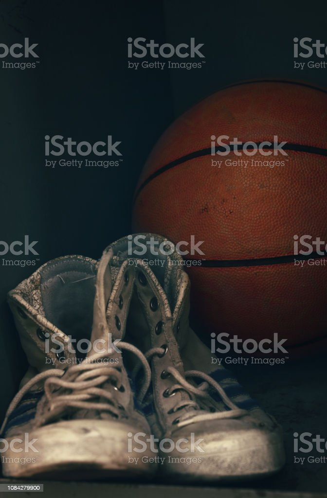 Close up pair of old worn sport sneakers shoes and one basketball...