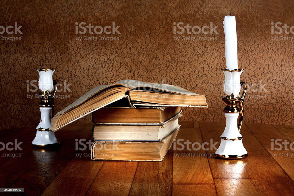 Old stack of books with candlestick and burning candle royalty-free stock photo