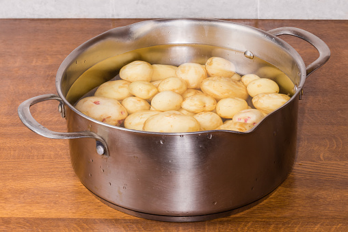 Open old stainless steel pot with raw young potatoes peeled from skin in cold water on a wooden kitchen table, close-up