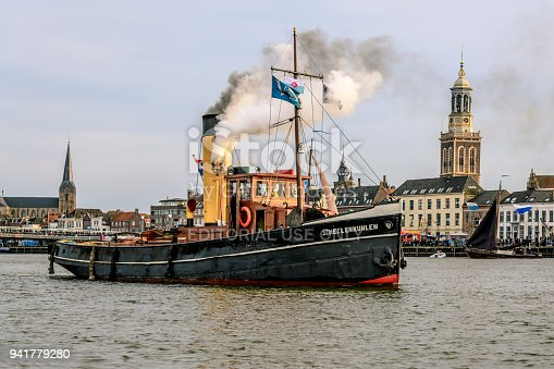 Old steam boat at the river IJssel during the 2018 Sail Kampen event in the Hanseatic league city of Kampen in Overijssel, The Netherlands. People on board are looking at the view and a crowd on the quay is watching the ships.