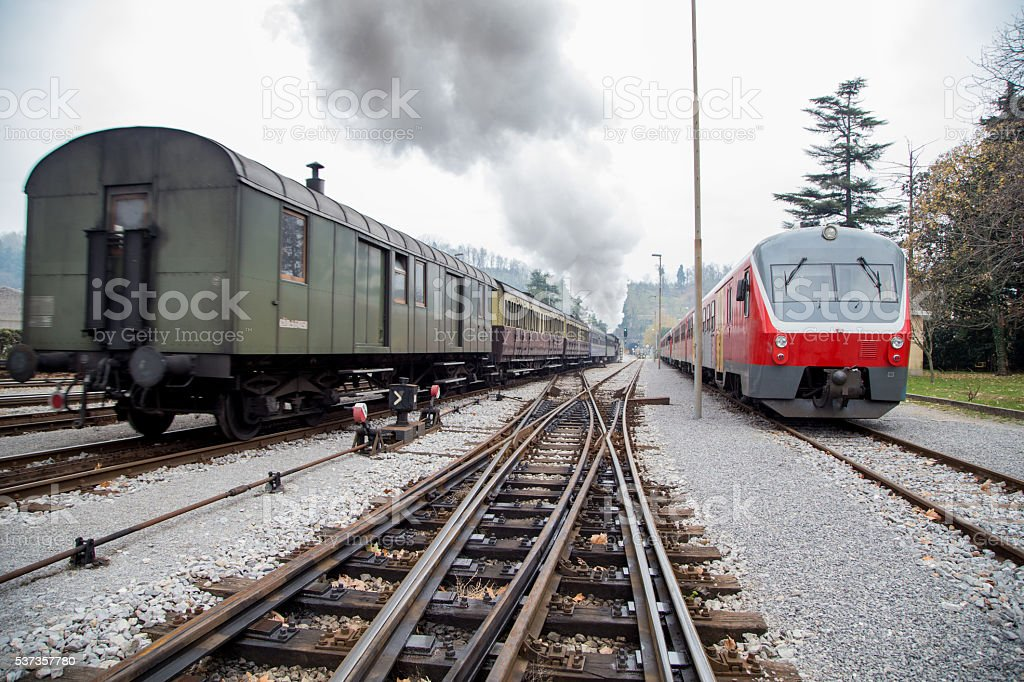 Old steam train and new electric train stock photo