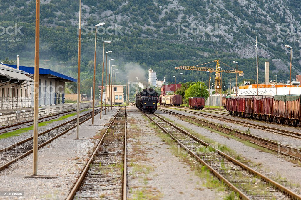Old steam train arriving at the station stock photo