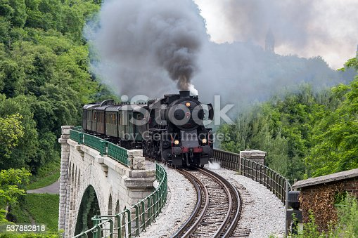 Old steam train crossing the Solkan bridge in Nova Gorica, Slovenia, Europe. Lots of black and gray steam hiding the locomotive, full frame, XXXL.