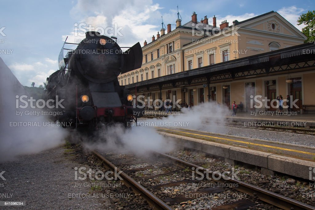 Nova Gorica, Slovenia - May 13, 2017: Old Steam Train on Railway Station of Nova Gorica, Slovenia. Old Steam Locomotive of black color is driving and leaving a lot of smoke from chimney and vapour. stock photo