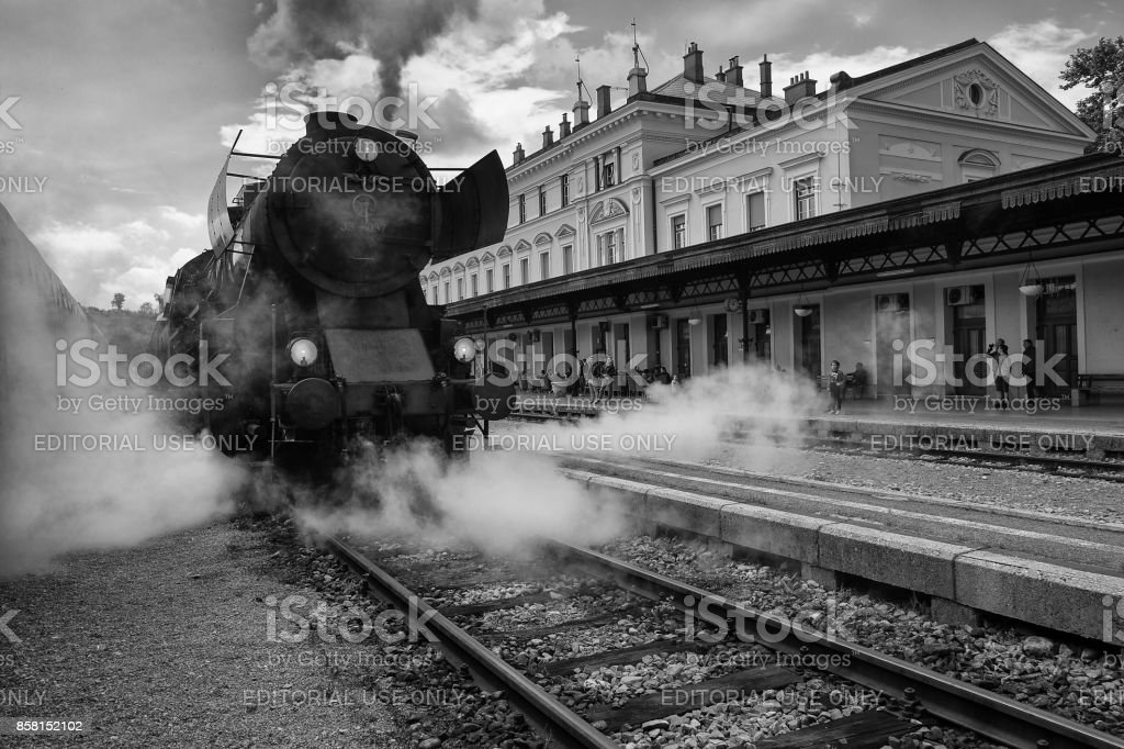 Old Steam Train on Railway Station of Nova Gorica, Slovenia. Old Steam Locomotive of black color is driving and leaving a lot of smoke from chimney and vapour. stock photo