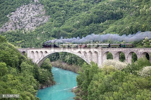 Old steam train on the Solkan bridge near Nova Gorica, Slovenia, Europe. Lots of black and gray steam hiding the locomotive, full frame.