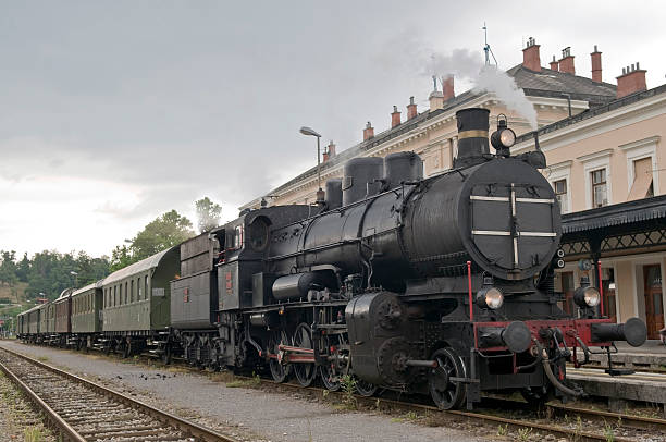 Old Steam Train  Ready to Depart Train with steam locomotive driving tourists, Slovenia, Europe. Cloudy day, train station in the background. depart stock pictures, royalty-free photos & images