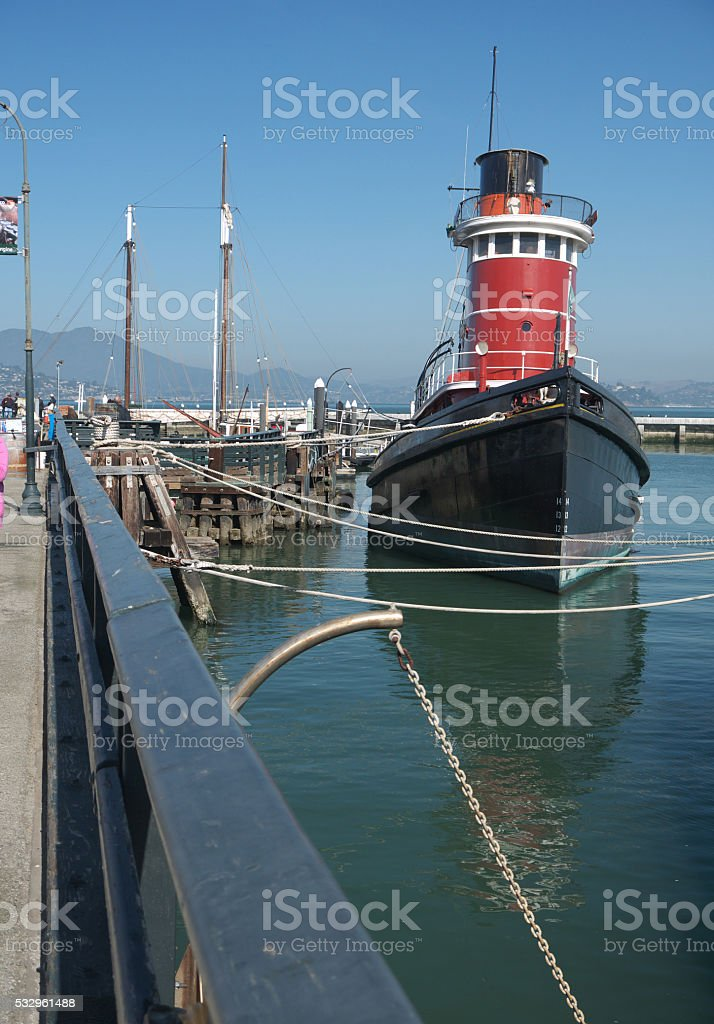 Old steam tugboat moored at pier stock photo