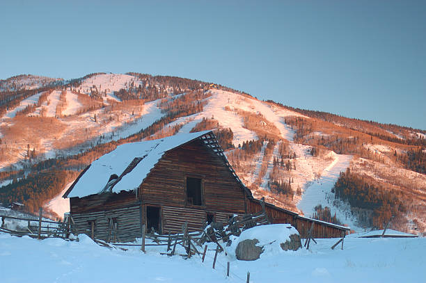 Old Steamboat Springs Barn, Ski Runs in Backdrop This is the somewhat famous steamboat springs bard located in the base village in the town of Steamboat Springs Colorado.  Sunset image.       steamboat springs stock pictures, royalty-free photos & images
