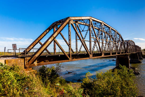 Old Steel Beam Railroad Bridge An Iconic Old Metal Truss Railroad Bridge over a Large River. railway bridge stock pictures, royalty-free photos & images