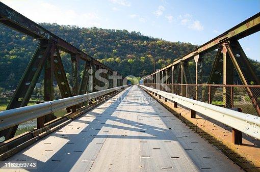 Rusty steel bridge across Dniester river in small village and mountains around. Ukraine.