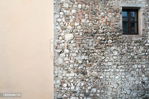 the contrast between an old stone wall flanked by a plastered wall