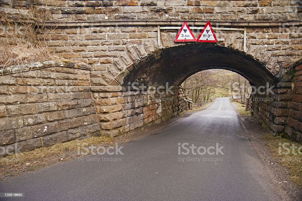 Old stone bridge over a country lane stock photo