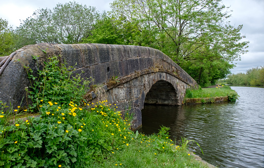 Old stone built pack horse bridge over the Leeds/Liverpool Canal, Lancashire, UK.