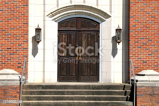 a set of old stone church wood doors and brick steps