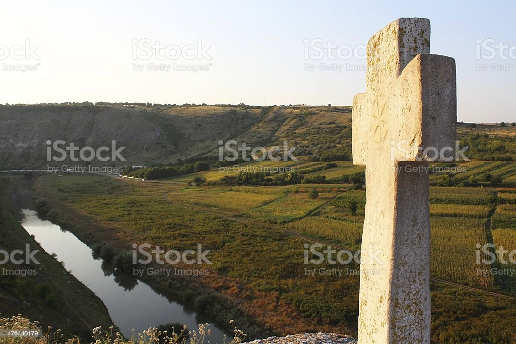 Old stone cross on the rock at sunset royalty-free stock photo