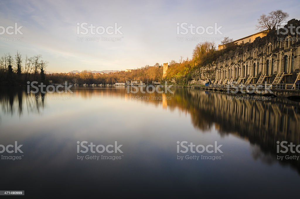old stone dam and trees reflected in water, long exposure stock photo
