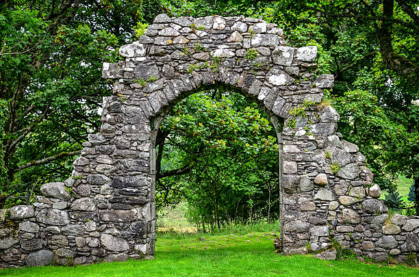 Old stone entrance wall in green garden stock photo