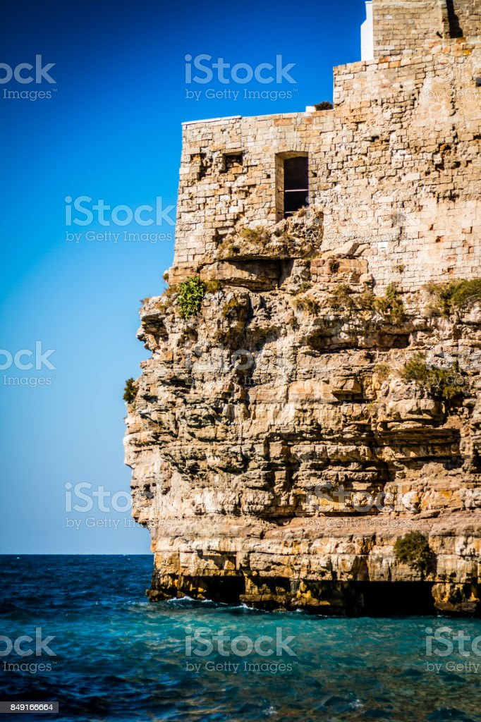 Old stone house on a cliff above the sea stock photo
