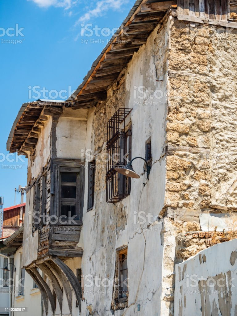 Old Stone House With A Wooden Gate And Windows On A Narrow Street In