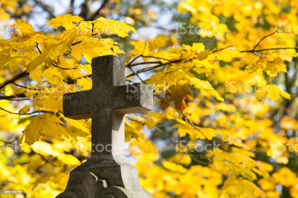 Old stone memorial cross at cemetery. Religious Christian symbol on autumn trees background stock photo