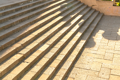 old stone stair architecture detail with sunlight with shade of people outline