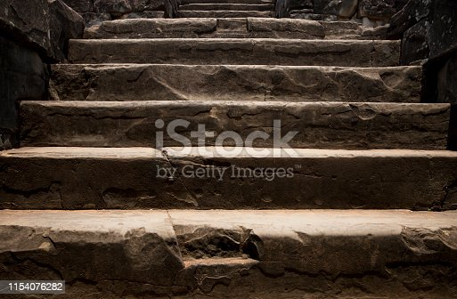 Old stone staircase. Ancient temple interior. Ancient stone stairs. Historic site concept photo for wallpaper or background. Rough staircase in Angkor Wat. Aged stone work with cracks. Tourist place