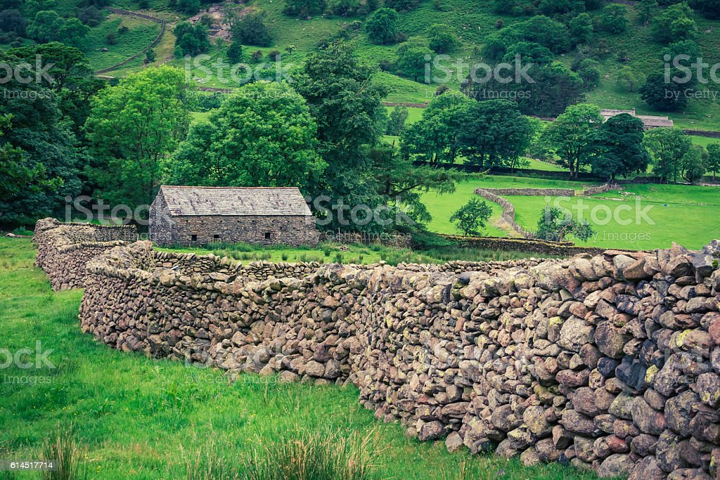 Old stone wall and house in the Lake District, England stock photo
