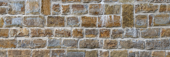 Old stone wall made of square, brown and gray natural stones in rows