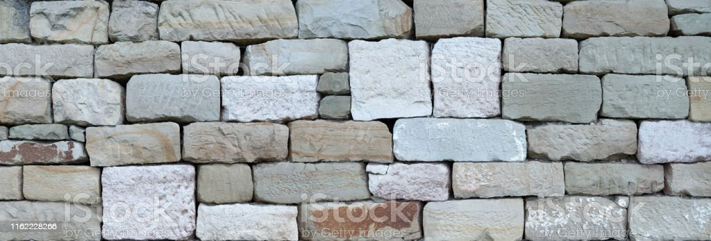 Old stone wall made of different, square hewn natural stones without...