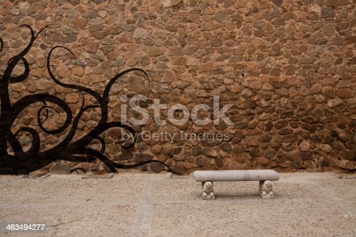 istock Old stone wall with bench and graffiti 463494277