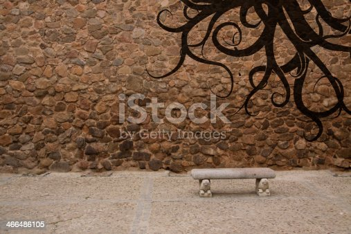 istock Old stone wall with bench and graffiti 466486105