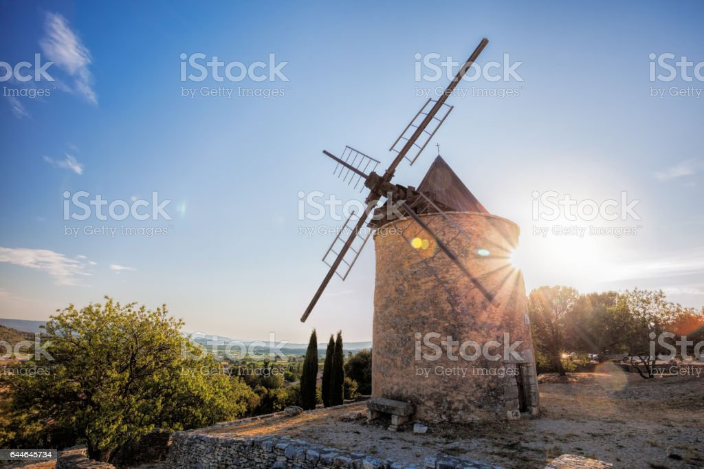 Old stone windmill against sunset in Saint Saturnin les Apt, Provence, France stock photo