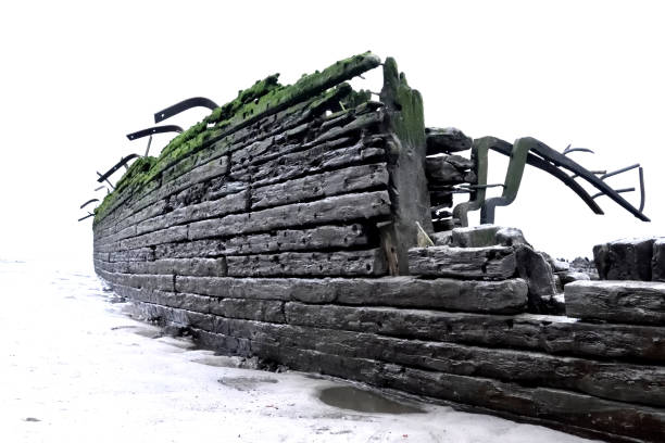 Old, stranded shipwreck on the beach Old, stranded shipwreck on the beach with weathered wood. Close-up of an ancient ship wreckage. Beach scene. Hamburg ,elbe river. sunken stock pictures, royalty-free photos & images