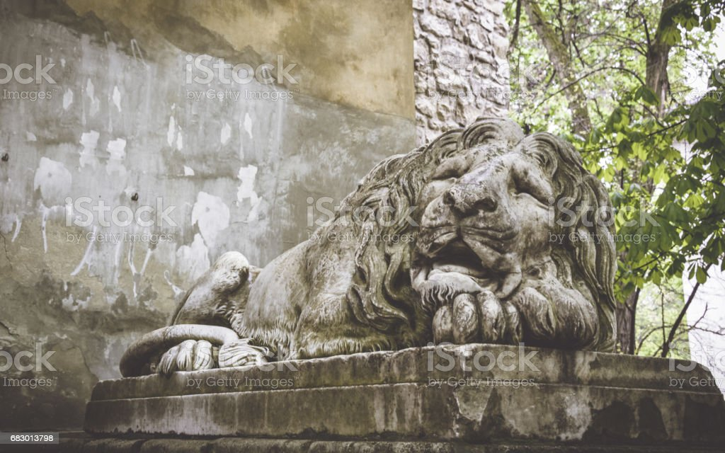 old street architecture of the city Lviv. A stone statue of a sleeping lion in the old Park royalty-free stock photo