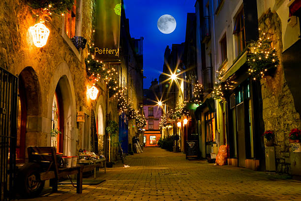 old street decorated with lights and full moon stock photo