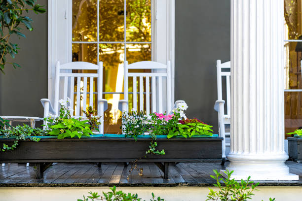 Old street historic Garden district in New Orleans, Louisiana with patio garden green plants flowers, white antebellum column and rocking chairs by mansion house Old street historic Garden district in New Orleans, Louisiana with patio garden green plants flowers, white antebellum column and rocking chairs by mansion house southern usa stock pictures, royalty-free photos & images