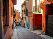 Lloret de Mar, Catalonia, Spain - October 14, 2013: The ancient street of the resort town steeply descends to the sea. Old multi-colored houses. Developed tourism.