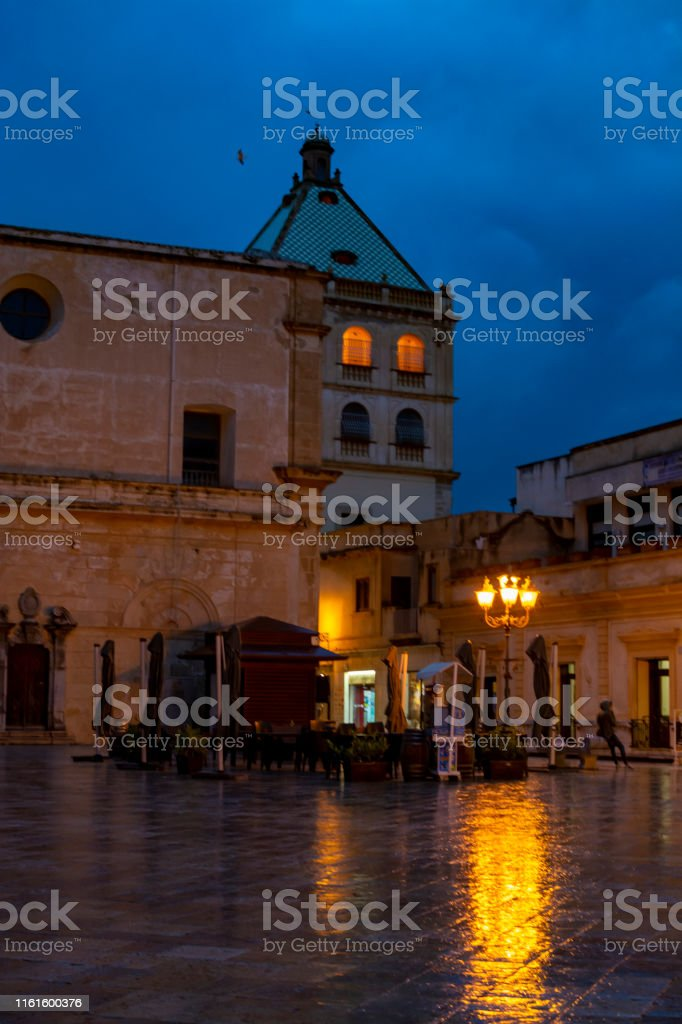 Old street in Marsala at night in rain with reflection of street...