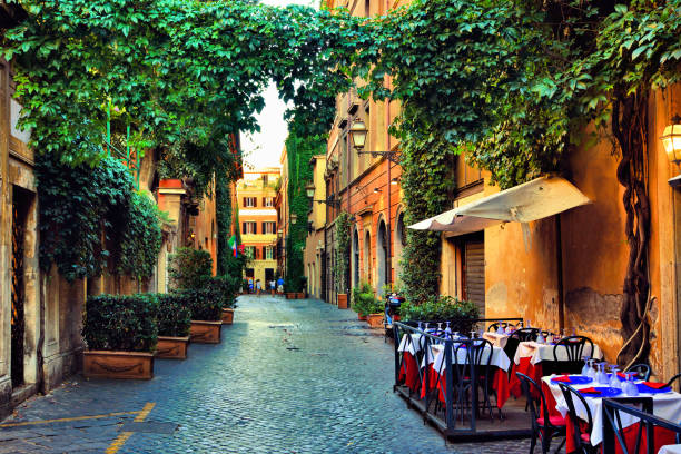Old street in Rome with leafy vines and cafe tables, Italy stock photo